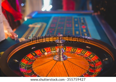 A close-up vibrant image of multicolored casino table with poker chips and roulette in motion, with the hand of croupier, and a group of gambling rich wealthy people in the background - stock photo