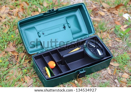 A close up view of an open tackle box showing different fishing lures and other gear - stock photo