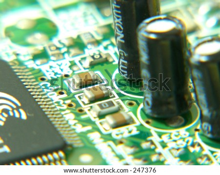 A close up view of circuit board with all kinds of electronic components attached. - stock photo