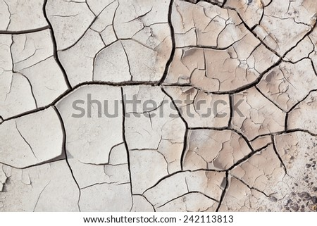 A close up view of dry cracked earth with layers pealing back and small pebbles. - stock photo