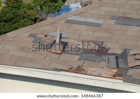 A close up view of shingles being blown off a roof and other roof damage - stock photo