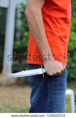 A close up view of someone wearing an orange shirt holding and griping a knife - stock photo