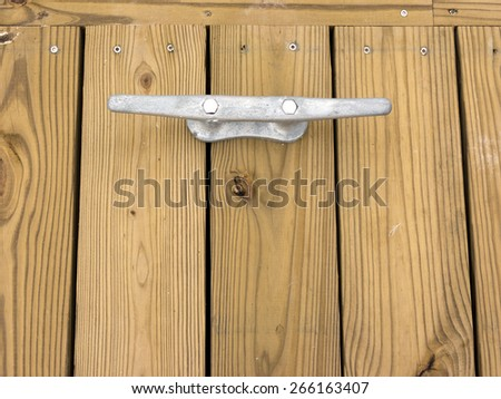 A close view of decking with boat cleat attached to dock. - stock photo