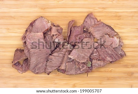 A close view of sliced leftover chuck roast on a wood cutting board. - stock photo