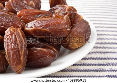 A close view of Tunisian pitted dates on a plate atop a striped table cloth. - stock photo