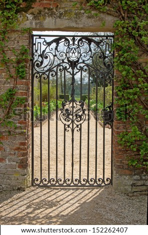 A closed gate looking onto a garden path with the gate design reflected in the shadow - stock photo