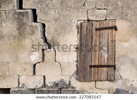 A closed wooden window of an old cracked house - stock photo