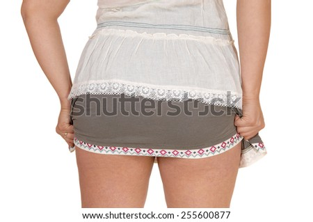 A closeup body part shot of a woman's back, holding her skirt, isolatedfor white background. - stock photo