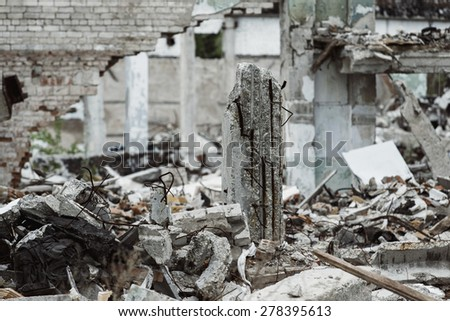 A closeup image of a ruined building with concrete and armature around. Concept of disaster, war. Retreat for homeless. - stock photo