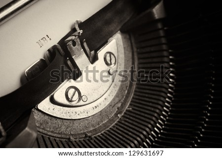 A Closeup image of the typebars and ribbon of an old style typewriter and paper with the letters: NB! (Shallow Depth of Field) - stock photo