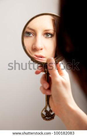 A closeup mirror reflection of a woman's face, selective focus - stock photo