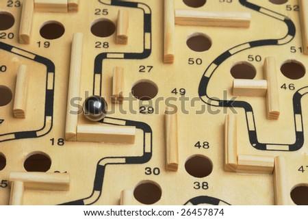 A closeup of a ball bearing navigating a wooden maze - stock photo