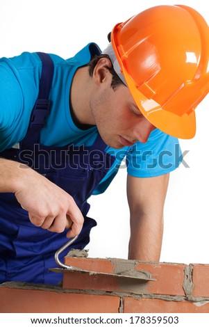 A closeup of a builder in orange helmet layering bricks - stock photo