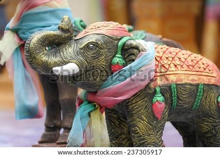 A closeup of a colorful carved elephant on a Buddhist shrine on the roadside of Kanchanaburi, Thailand. - stock photo