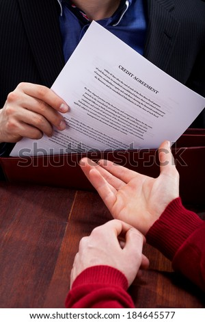 A closeup of a credit angreement document being given to a client - stock photo