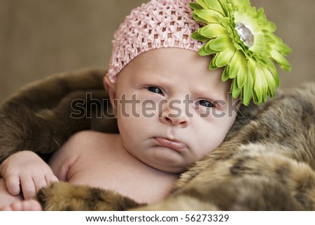 A closeup of a cute frowning baby girl wearing hat with flower, selective focus with shallow depth of field - stock photo