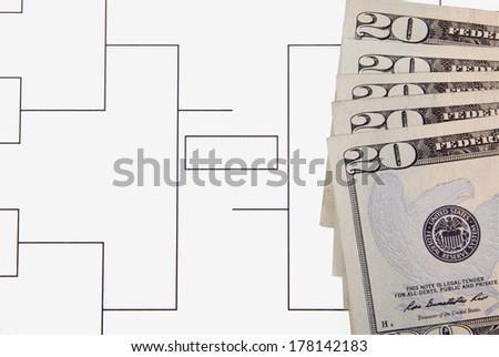 A closeup of a final four bracket and twenty dollar bills. - stock photo