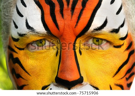 A closeup of a man's face painted like a tiger. - stock photo