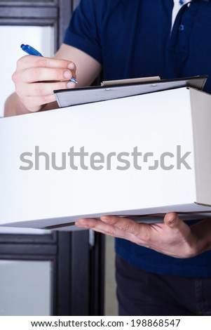 A closeup of a man signing a package that came in the post - stock photo