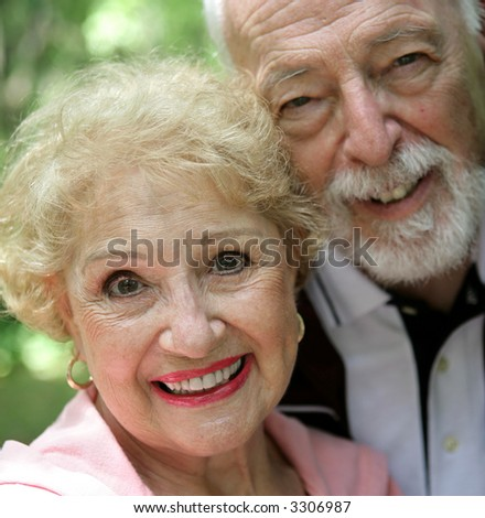 A closeup of a pretty senior woman in pink with her loving husband by her side.  Could be used for breast cancer awareness. - stock photo