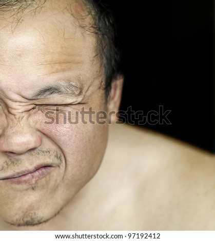 A closeup of a rugged sun tanned oriental man face grimacing. - stock photo