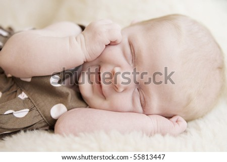 A closeup of a sleeping three week old baby girl smiling, soft focus - stock photo