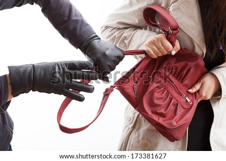 A closeup of a thief wearing gloves holding a woman's bag - stock photo
