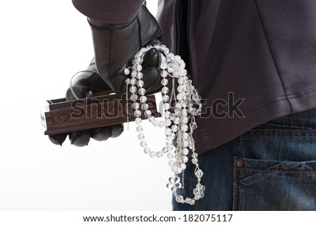 A closeup of a thief with stolen pieces of jewelery - stock photo