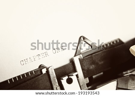 """A closeup of an old fashioned typewriter with the words """"CHAPTER ONE"""" clearly visible. - stock photo"""