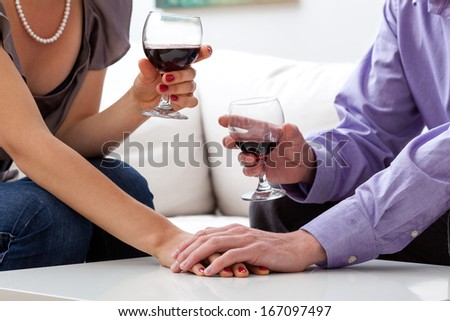A closeup of lovers drinking a glass of red wine - stock photo