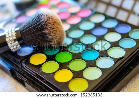 A closeup of makeup brush and color palette - stock photo