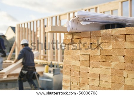 A closeup of stacks of 2x4 boards at a construction site, with a roll of blueprints sitting on top.  Two construction workers and building frame can be seen in the background. Horizontal shot. - stock photo