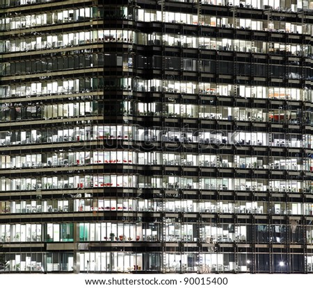 A closeup of the facade of a modern skyscraper showing business activity on each level of the building for the concept of vertical city, in Canary Wharf, London. - stock photo