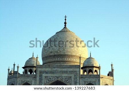 A closeup  of the Taj Mahal dome. Taj Mahal is a mausoleum built by the Mughal emperor Shah Jahan for his wife Mumtaz Mahal in the city of Agra. - stock photo