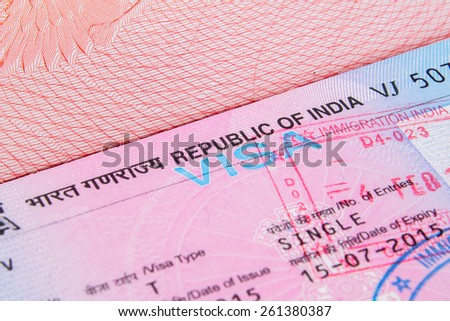 A closeup of used Indian tourist visa vignette inside a passport. Shallow DoF with focus on the word VISA single with immigration stamp  macro - stock photo