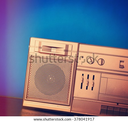A closeup or a speaker of a retro gold boombox eighties stereo with a blue background for a music or sound concept. - stock photo