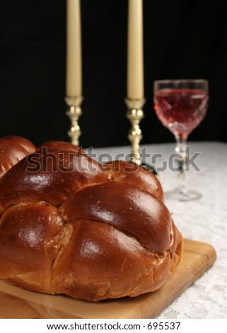 A closeup photo of challah bread for Shabbat with wine and candles in the background.  Vertical over black. - stock photo