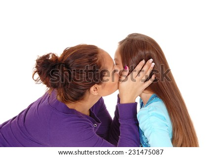 A closeup picture of a mother kissing her little daughter on the chick, isolated for white background.  - stock photo