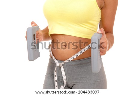 A closeup picture of the stomach on a teen girl with weights in her hand, body part isolated on white background.  - stock photo