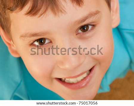 A closeup portrait of a smiling boy; focus on the eyes - stock photo