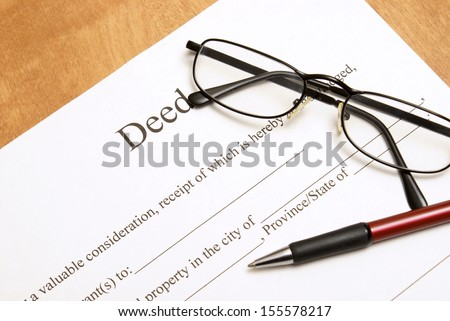 A closeup shot of deed papers and glasses to read the fine print. - stock photo