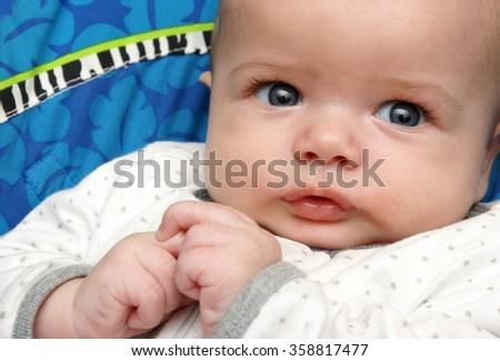 A closeup view of a handsome baby boy resting casually and fully alert. - stock photo