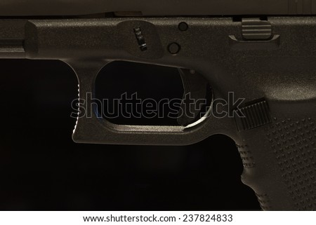 A closeup view of a semi-automatic pistol trigger. On black background. - stock photo