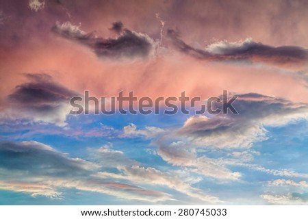 A cloudy sky is painted with vivid colors at sunset. - stock photo