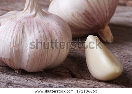a clove of garlic and a whole wooden table closeup - stock photo