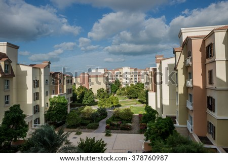 A cluster of buildings with green landscaping in a residential community from Dubai. - stock photo