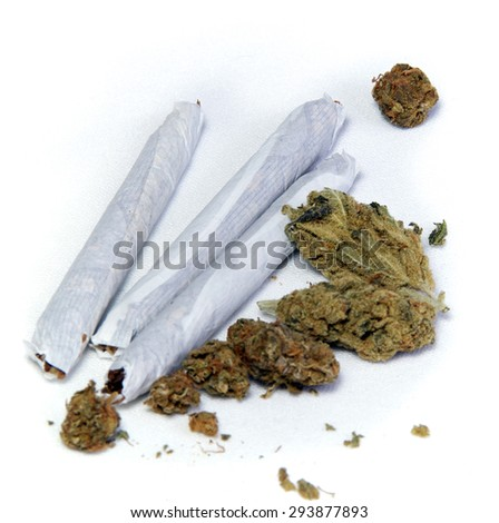 A cluster of marijuana buds and three joints up close over white. - stock photo