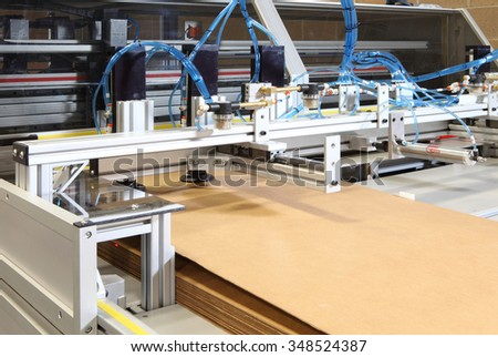 A CNC machine to cut and score corrugated cardboard boxes. - stock photo