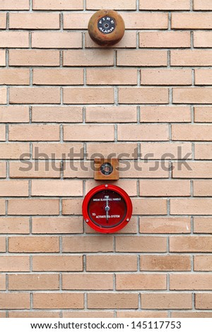 A CO2 fire alarm break glass system mounted on a brick wall.  - stock photo