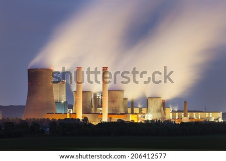 A coal-fired power station in the distance at night. The power station Niederaussem has the second highest cooling tower in the world with a height of 200m. - stock photo